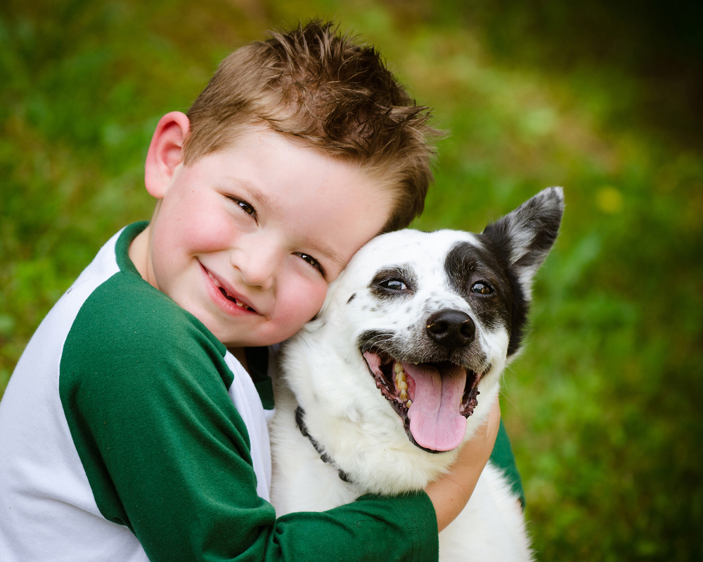 young boy hugging his small dog